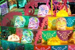 Decorative sugar skull lanters line a river barge during the parade.