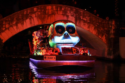 A decorated river barge floats along the San Antonio River.
