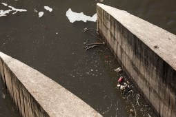 Small debris passes by Olmos Dam as larger trash is held by rakes.