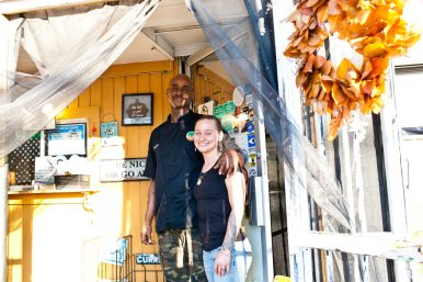 Gus and Shannon Bard, husband and wife and co-owners of Sweet Yams, stand in the entrance to their restaurant.
