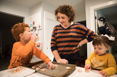 (From left) Lincoln Ripper, 3, eats a cookie from the baking sheet as he, Marcie Trevino Ripper, and Austen Ripper, 18 mo., lay out cookies to bake.