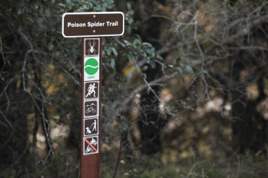 A trail marker indicates proper uses and the route of Poison Spider Trail.