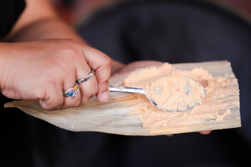 Masa is spread across a cornhusk with the back of a spoon.