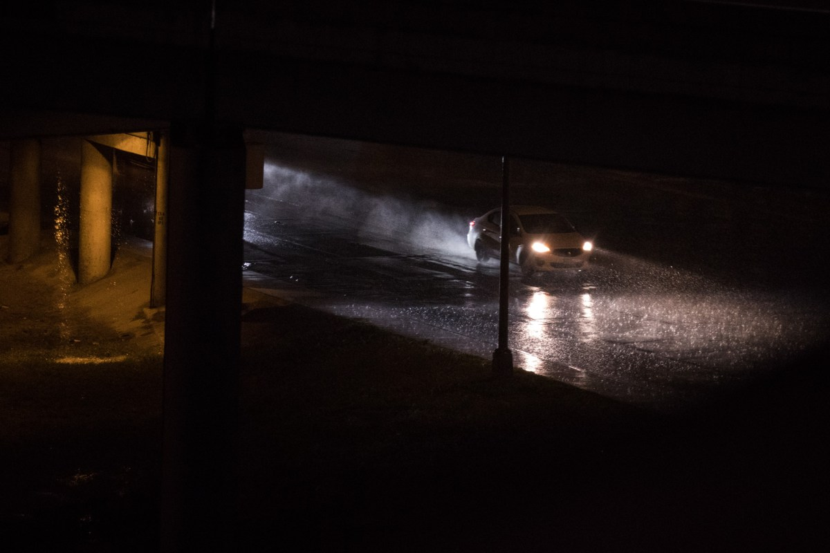 A car drives along Broadway Street during the flash flood warning in San Antonio on Sunday evening.