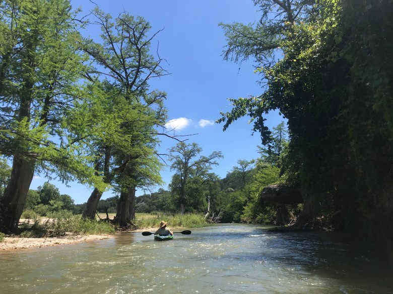 Rye Druzin rides a kayak down the Guadalupe River near Sisterdale.