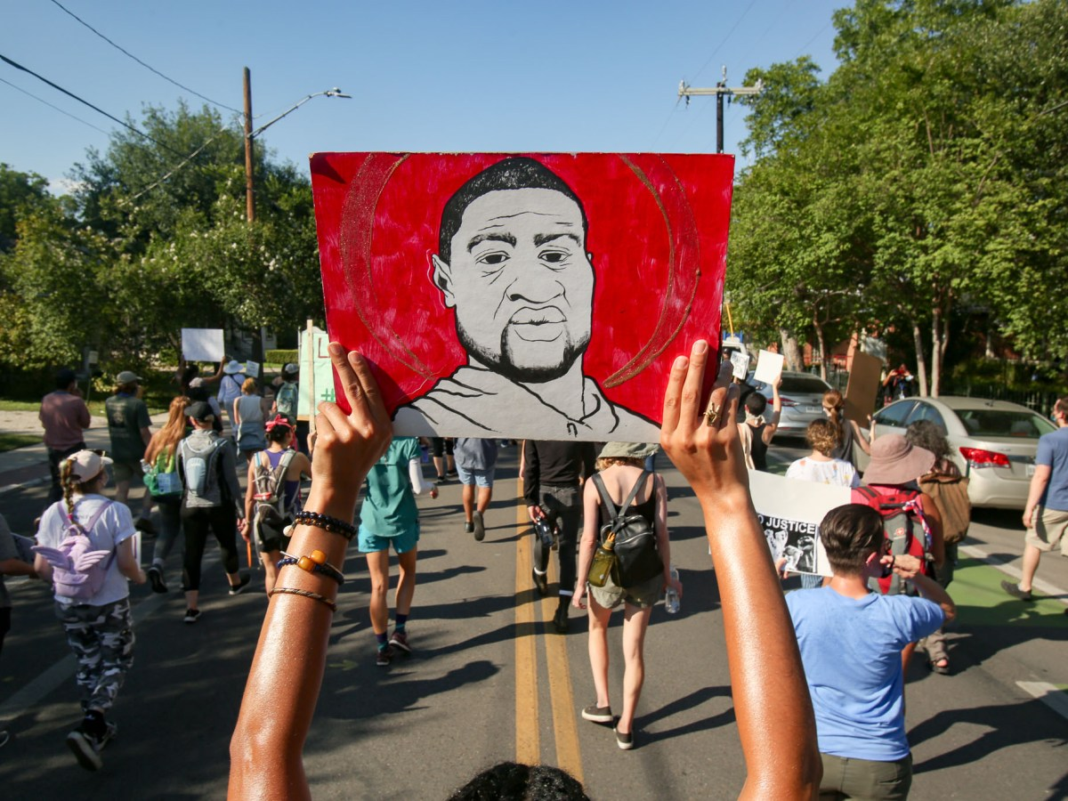 A demonstrator holds a painting of George Floyd, whose death sparked a national movement for police reform, during a Black Lives Matter march in Southtown.