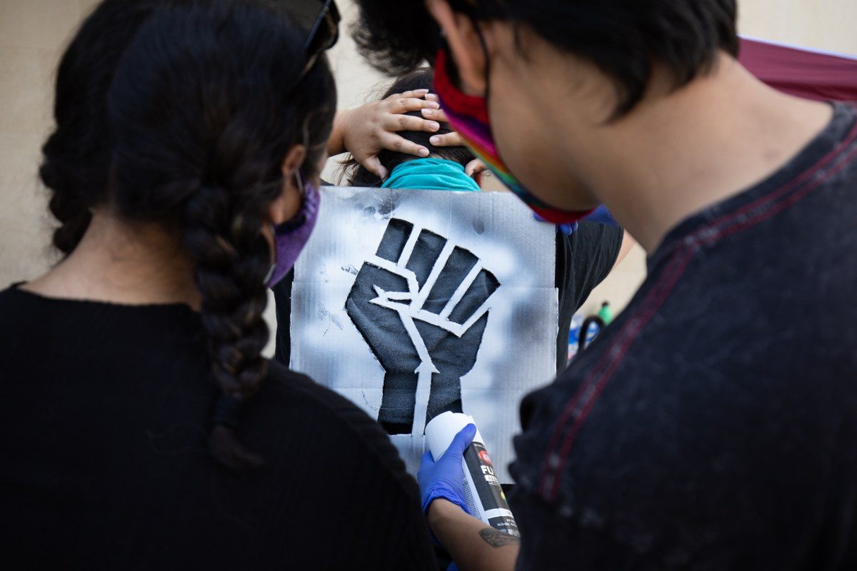 Michael Alvarez (right) spray-paints the back of a T-shirt with a raised fist cutout in support of Black Lives Matter as Ariel Alvarez holds the stencil.