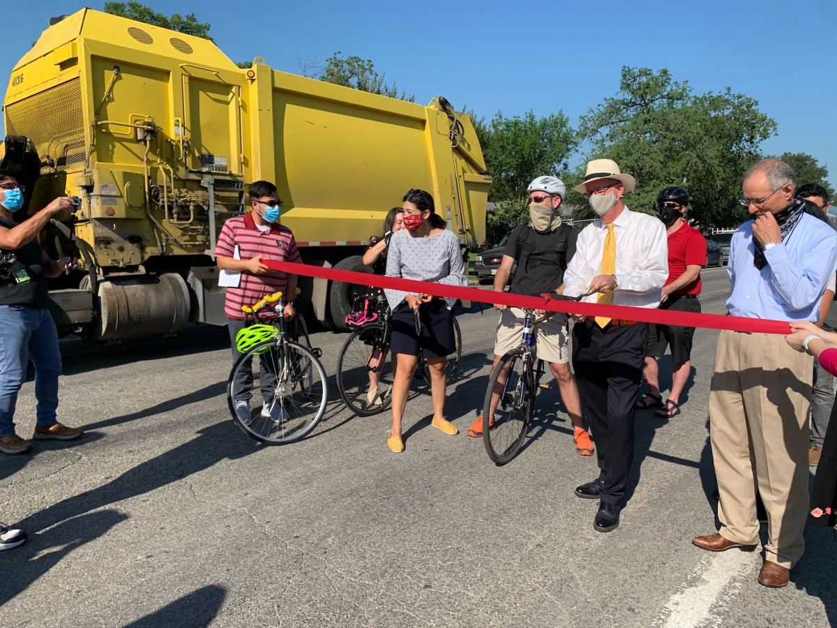 """A recycle collection truck passes by as Councilwoman Ana Sandoval (D7) and St. Mary's University President Tom Mengler prepare to cut a ceremonial ribbon for the launch of the 'Share the Streets"""" pilot program on Cincinnati Avenue."""