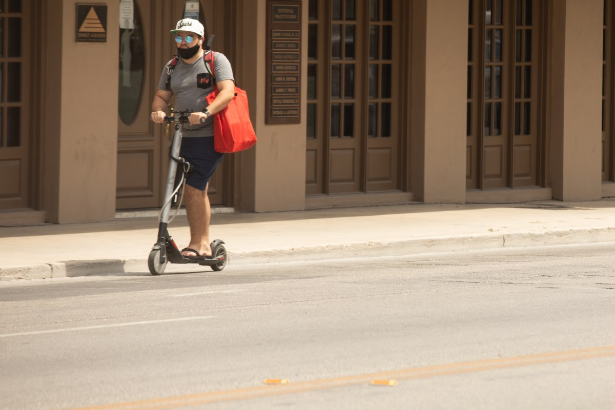 A man wearing a mask rides a scooter along South Flores Street.
