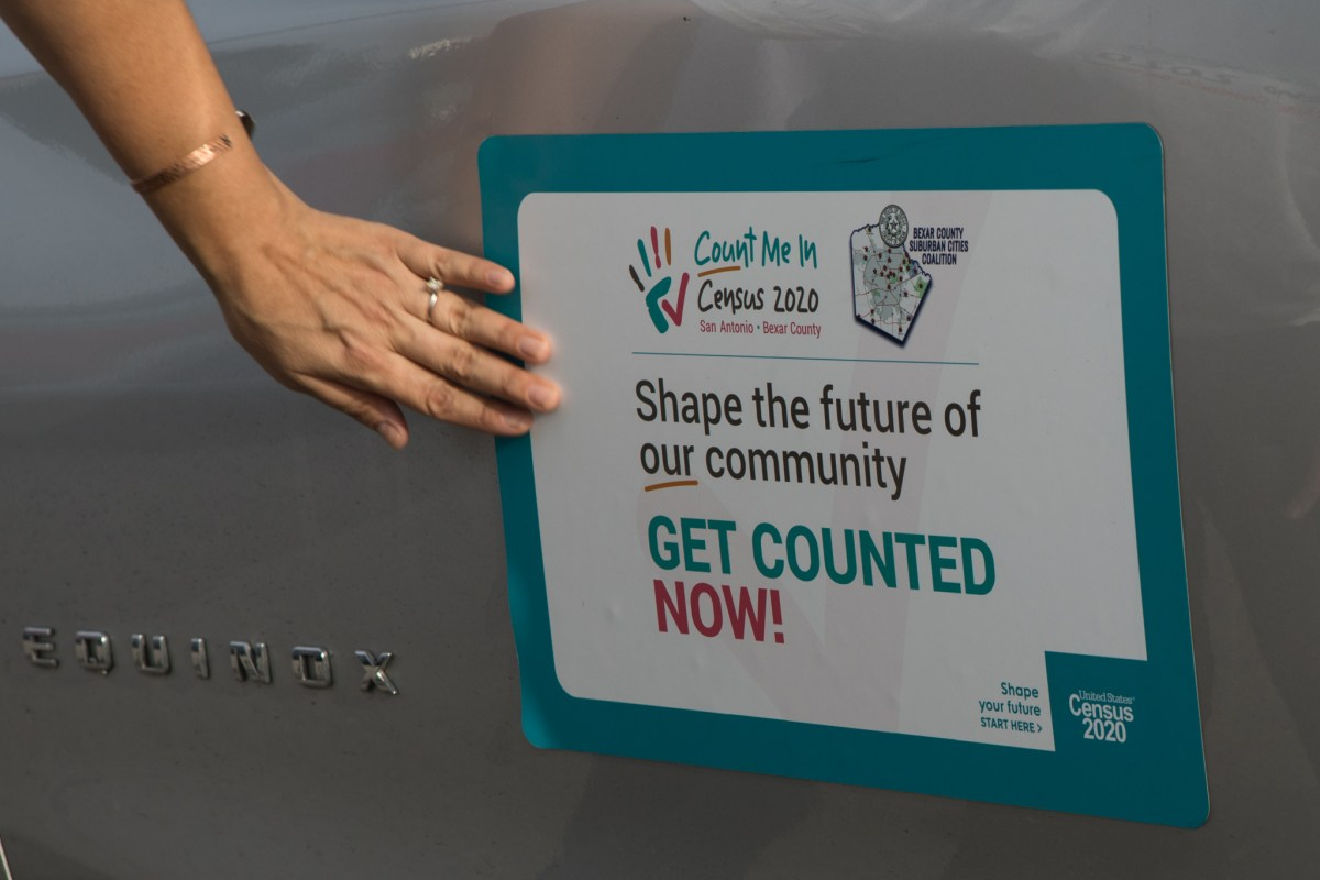 Queta Rodriguez places decorations promoting the census on her car before LULAC District 15 of San Antonio and U.S. Census Bureau's car caravan on the West Side on Aug. 1.