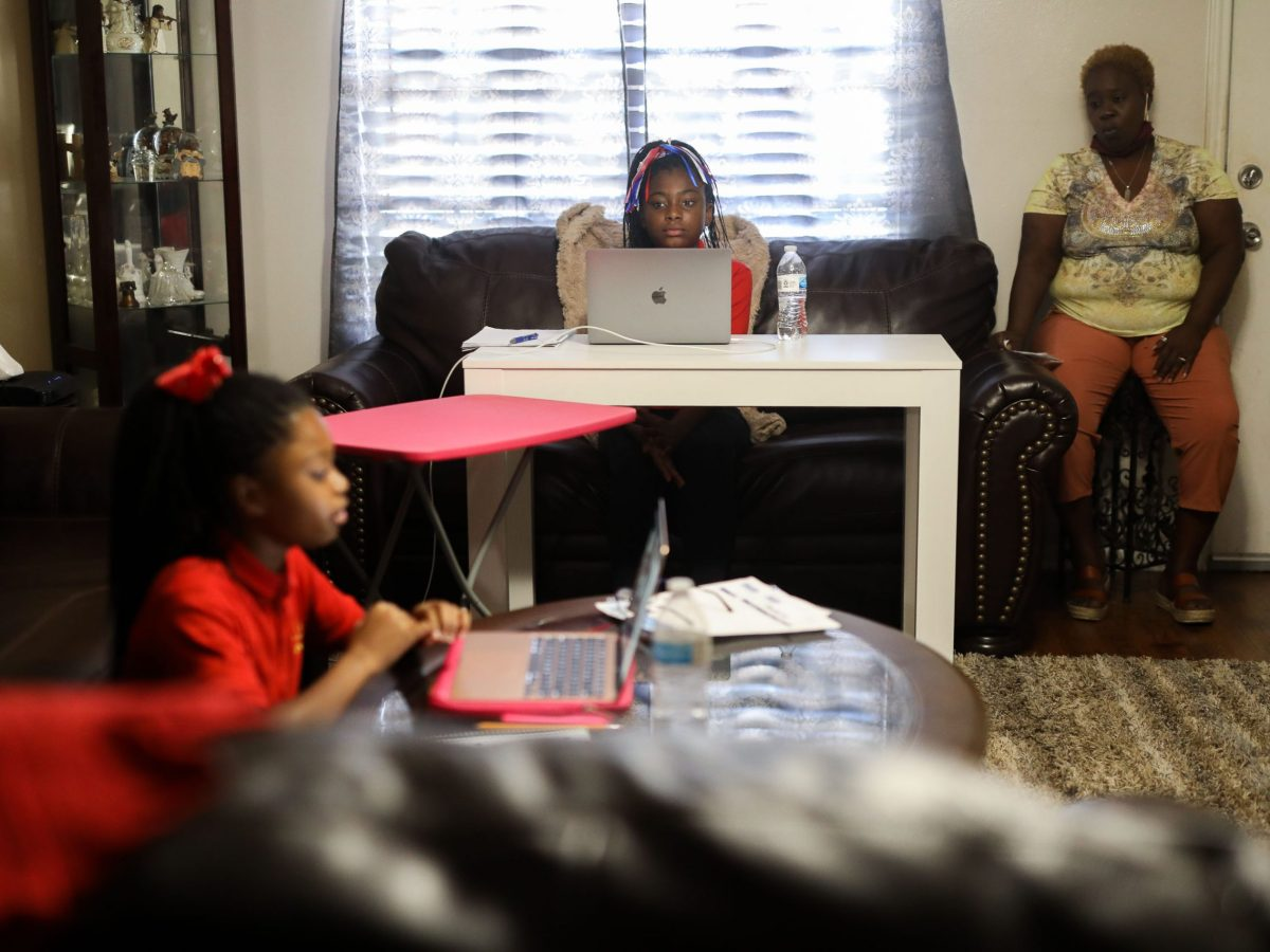 Kandis (left) and Keiaja Davis work with classmates virtually during a homeroom period at IDEA Eastside's online classroom as their mother, Yolanda Davis, observes.