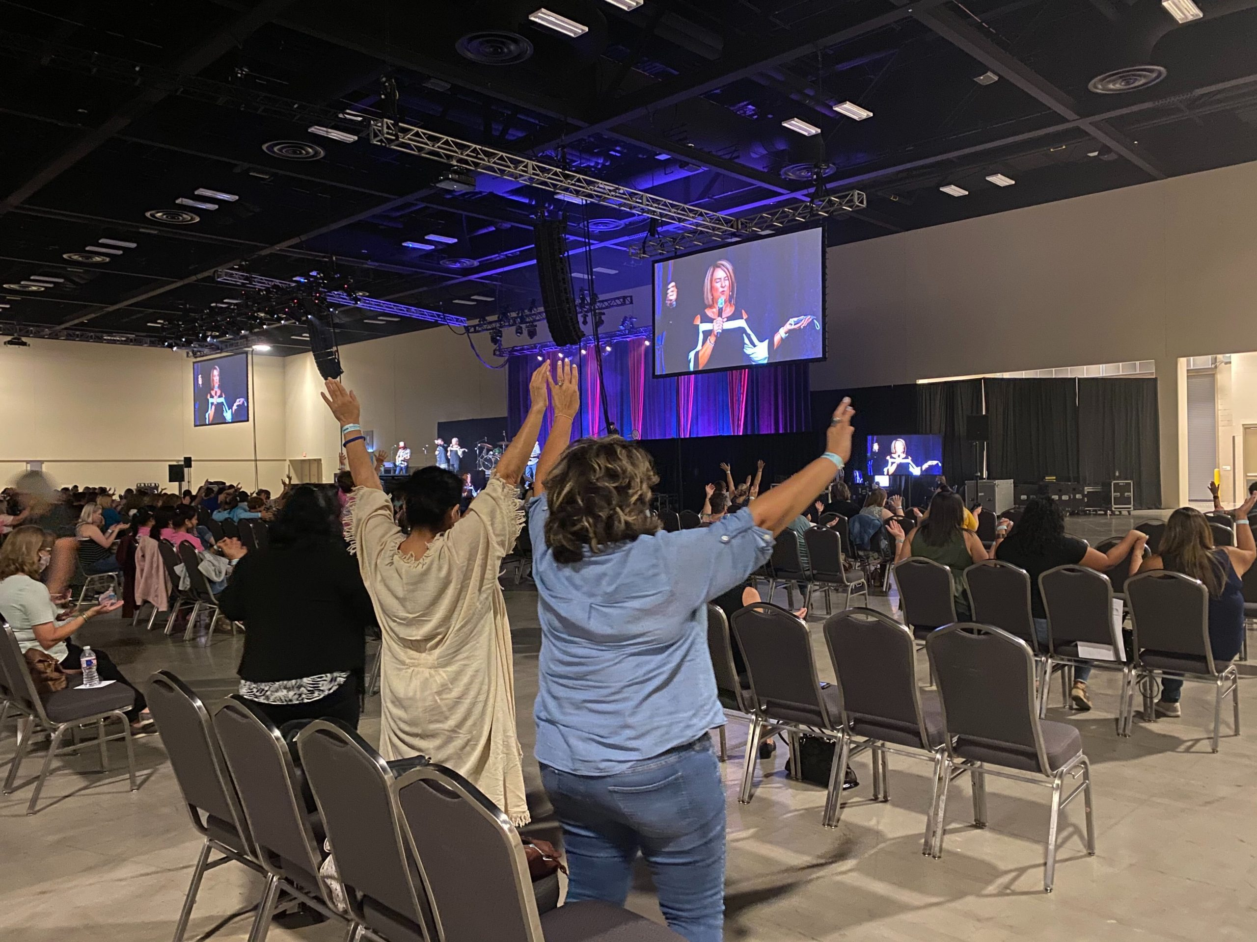 Attendees raise their hands in prayer during the Women of Joy conference at the Henry B. González Convention Center.