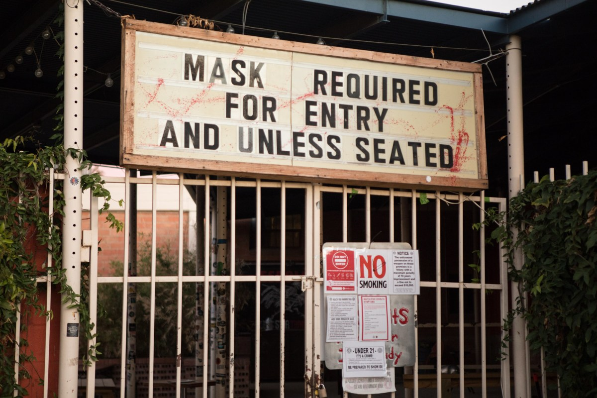 """A sign on N. St. Mary's St. says, """"mask required for entry and unless seated."""""""