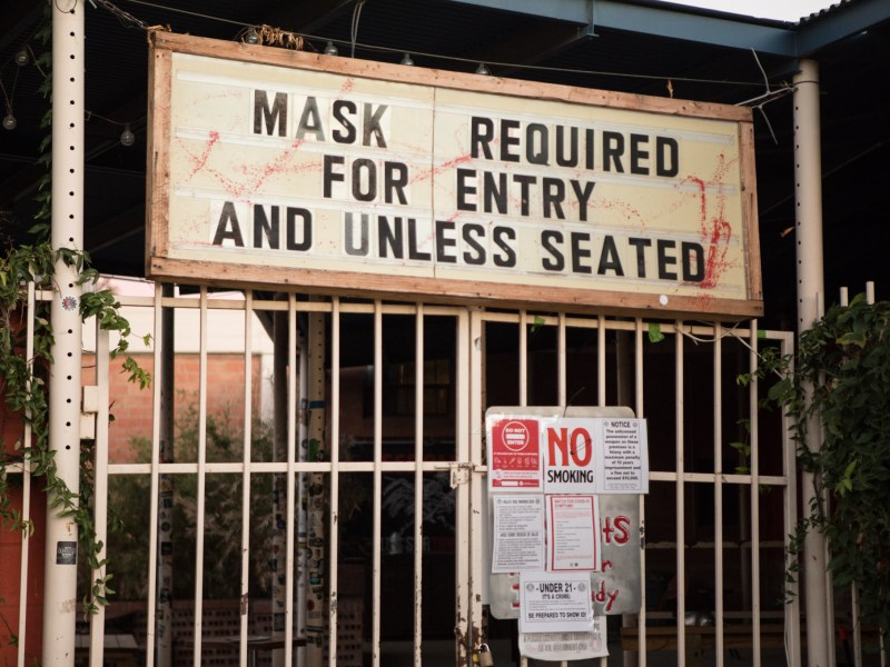 "A sign on N. St. Mary's St. says, ""mask required for entry and unless seated."""