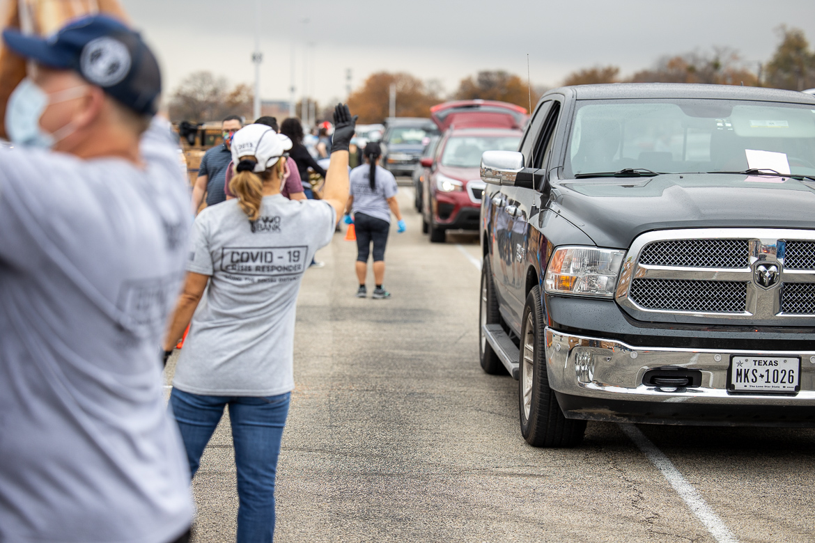 A volunteer signals for a vehicle to pull forward at the San Antonio Food Bank food distribution.