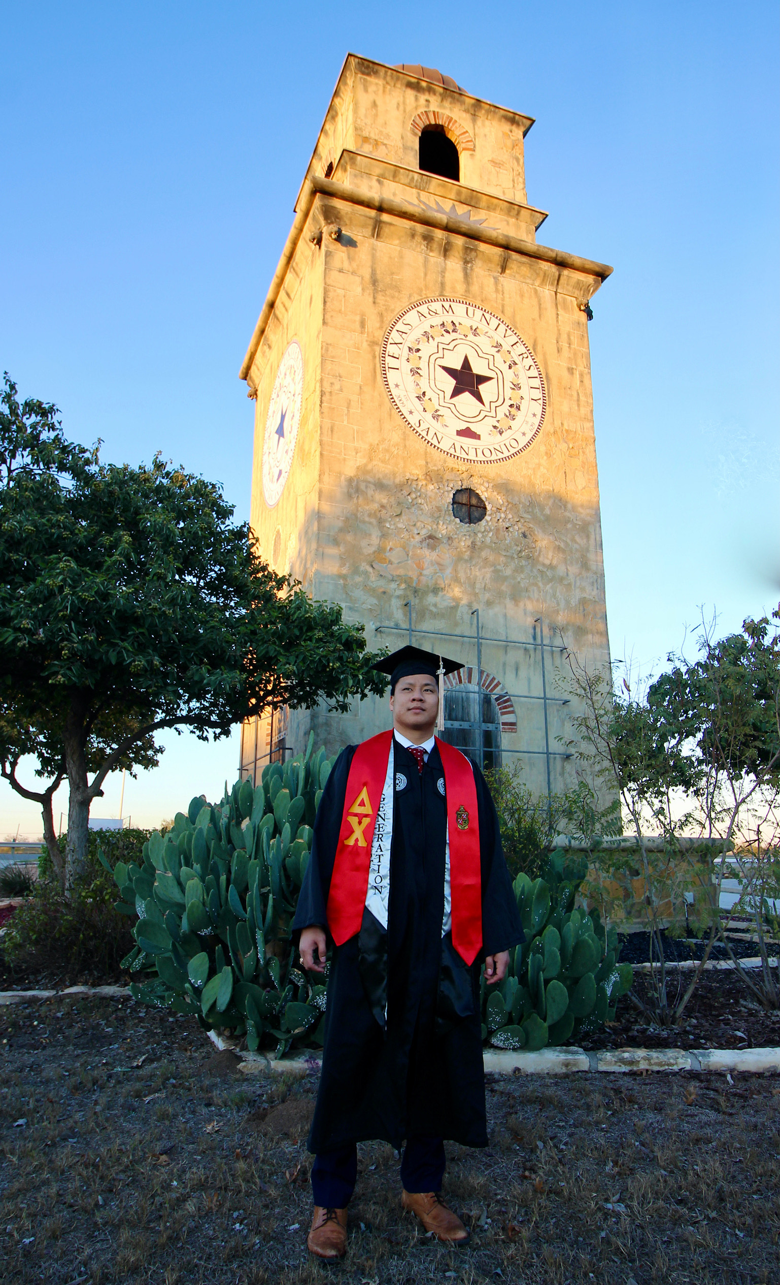 Ken Huynh poses in his graduation robe in front of the Torre de Esperanza (Tower of Hope) at the entrance to Texas A&M University San Antonio Dec. 2020.