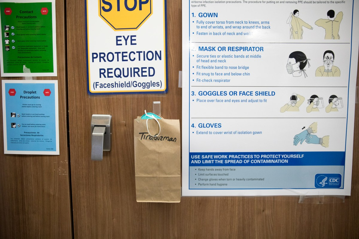 A paper bag taped to a patient's door stores an N-95 mask that can only be used a certain number of times before it needs to be replaced.