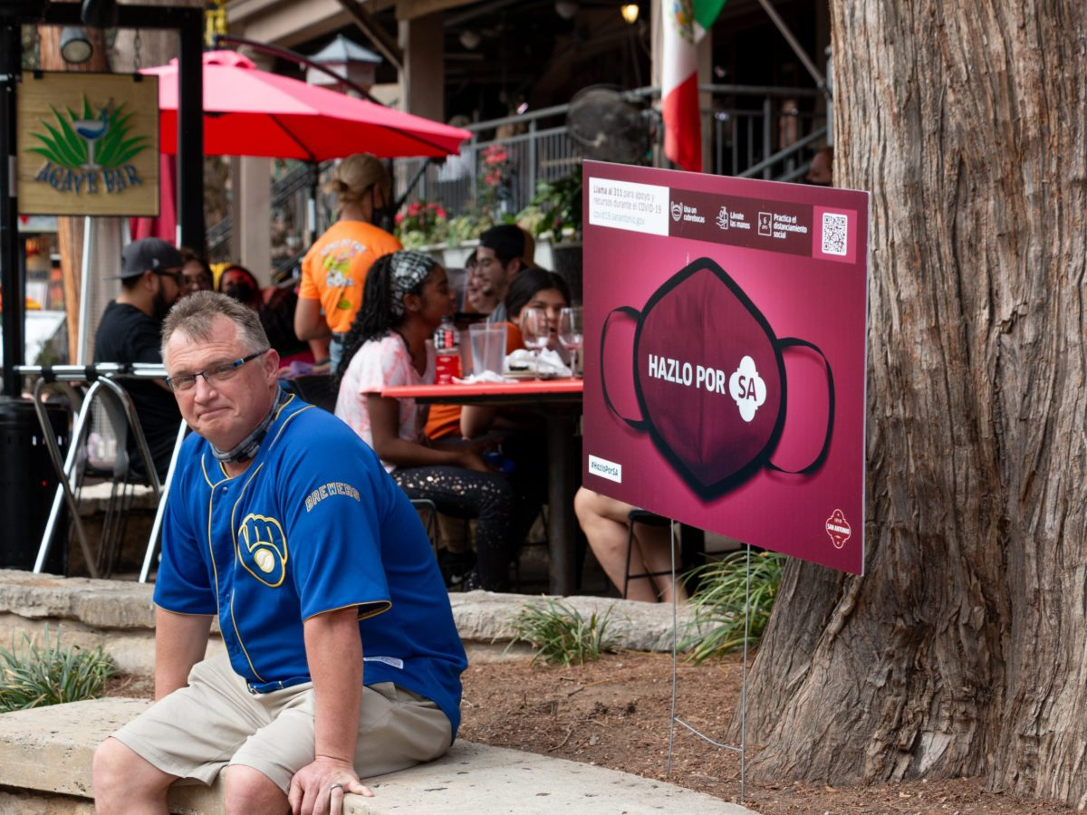 """A maskless man sits next to a sign that says """"Do it for SA"""" in Spanish over an image of a facemask. Many visitors descended upon the San Antonio Riverwalk during Spring Break. Some chose to wear masks and others went without. Tuesday, March 16, 2021."""