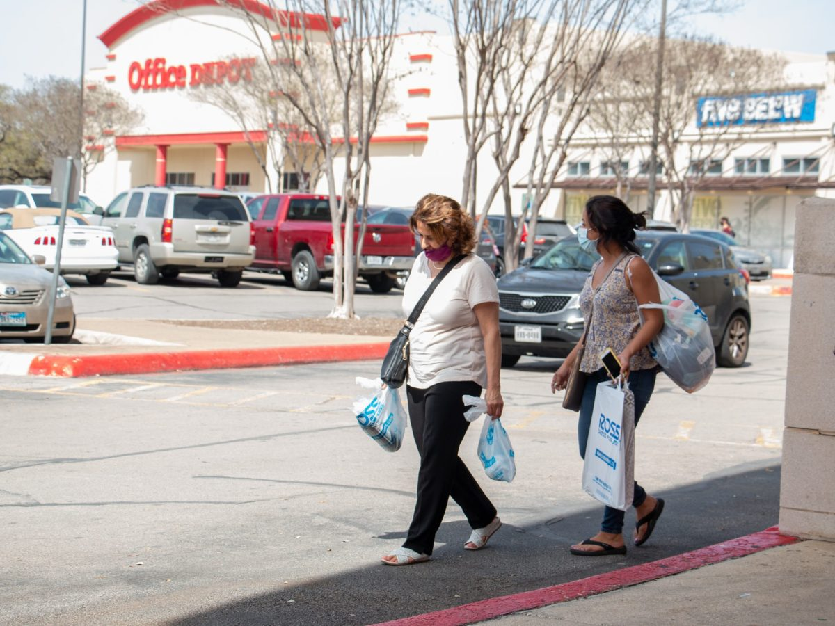 Two shoppers leave a store in the Northwoods Shopping Center. Monday, March 15, 2021.