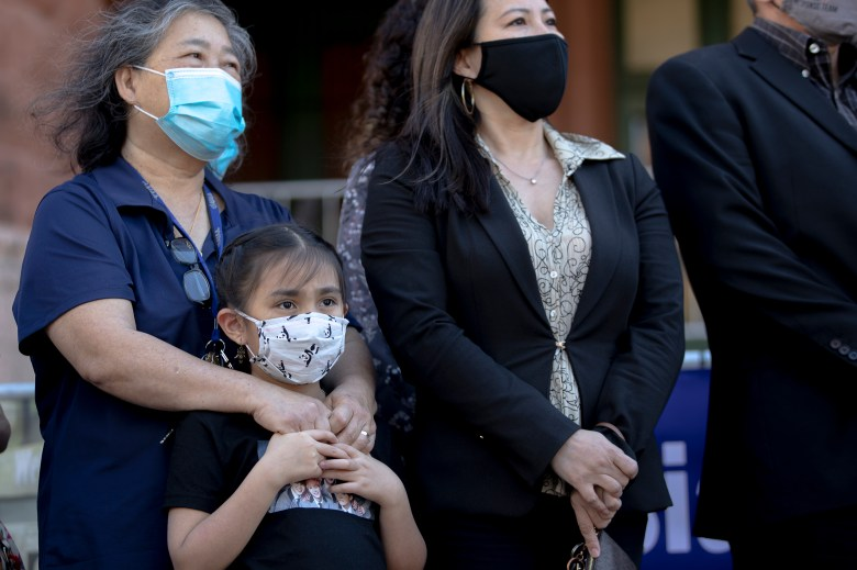 Margaret Lew holds her 9-year-old grandaughter, Janessa, during a press conference outside the Bexar County Courthouse on Thursday, March 18, 2021, in San Antonio, Texas. District Attorney Joe Gonzales held a press conference to denounce hate crimes perpetrated against Asians and committed to fully prosecute the individuals responsible for racist graffiti painted on the entrance to Noodle Tree, a Northwest Side ramen restaurant.