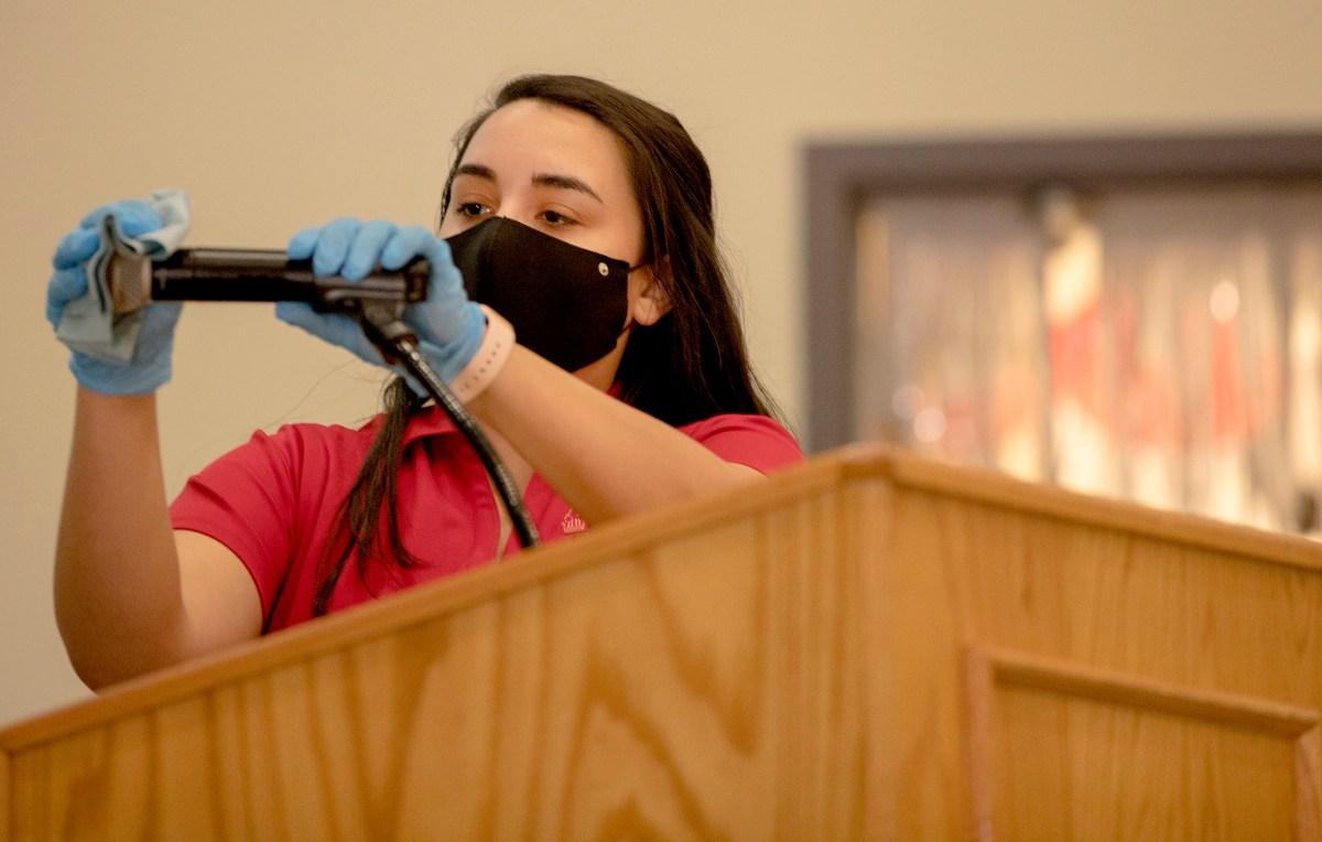 Alyssa Alfaro sanitizes a microphone at University of Incarnate Word's School of Osteopathic Medicine.