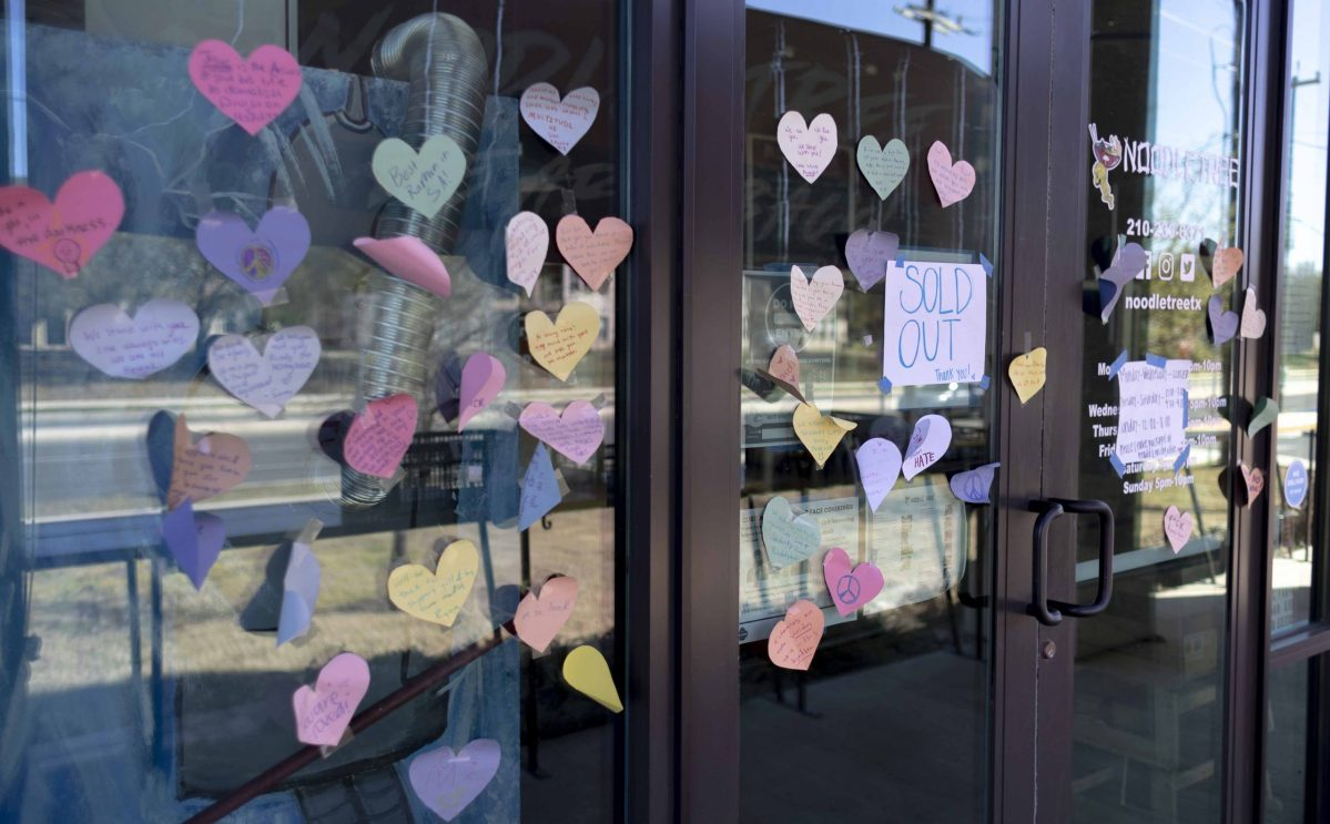 Paper hearts with supportive messages are taped onto the windows of Noodle Tree, an Asian American-owned ramen restaurant vandalized Sunday with racist graffiti.