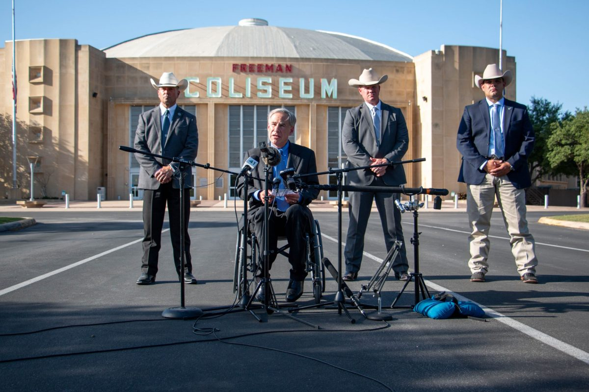 Gov. Greg Abbott is flanked by Texas Rangers during a press conference outside the Freeman Coliseum where he announced an investigation into reports that an undisclosed number of unaccompanied migrant youths have been abused or neglected at the facility.