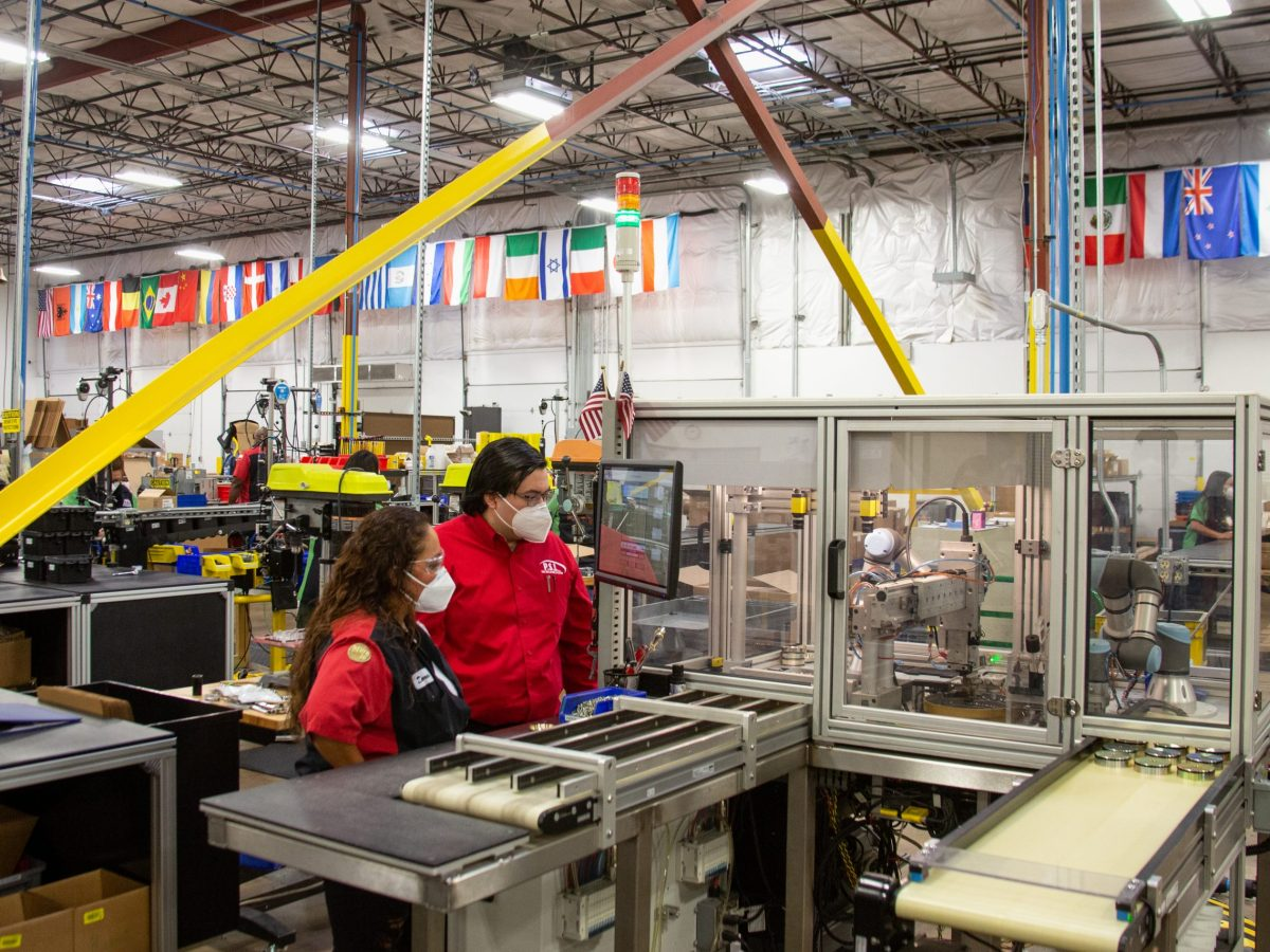 Dolores Guerra-Macias and John Torres oversee a robot on the factory floor at Pressure Systems International (PSI). Because they are not fully automated, PSI's robots require human workers to collaborate with them to complete each task.