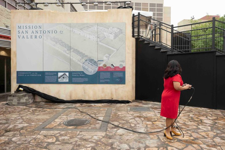 Councilwoman Rebeca Viagran (D3) activates a mechanical drop curtain unveiling a historical guide on the Losoya home. Viagran is a descendent of the Losoya family.