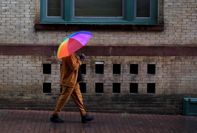 A man walks down a sidewalk during a rain storm on Friday.