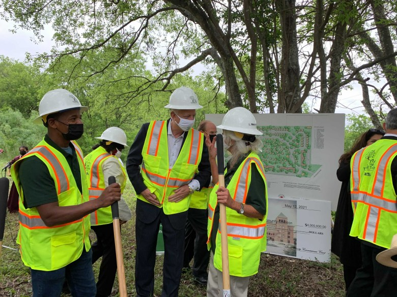Housing First Community Coalition Director Chris Plauche (right, center) speaks with philanthropist Gordon Hartman while coalition board member Aaron Green (left) looks out over the property slated to become Towne Twin Village.