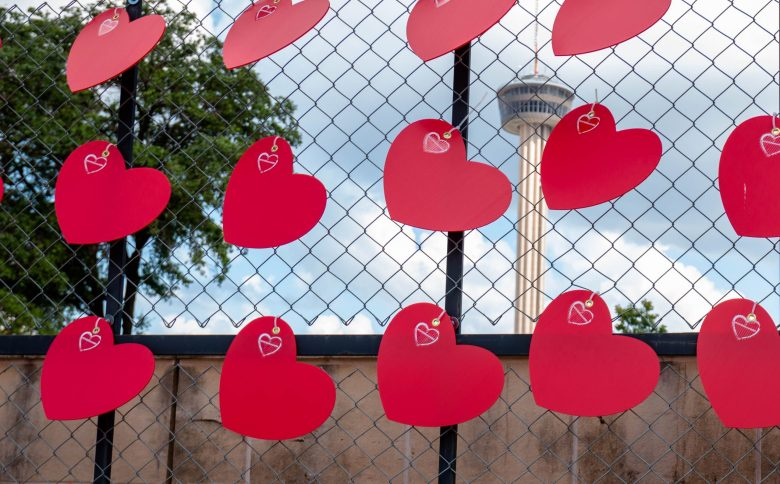 """The Tower of the Americas stands tall in the distance behind the center point of the """"Deep in Our Hearts"""" COVID Memorial, organized by the San Antonio Community Resource Directory. Each heart represents a life lost to COVID-19 in San Antonio. Familes can come and decorate a heart to honor their lost loved-one."""