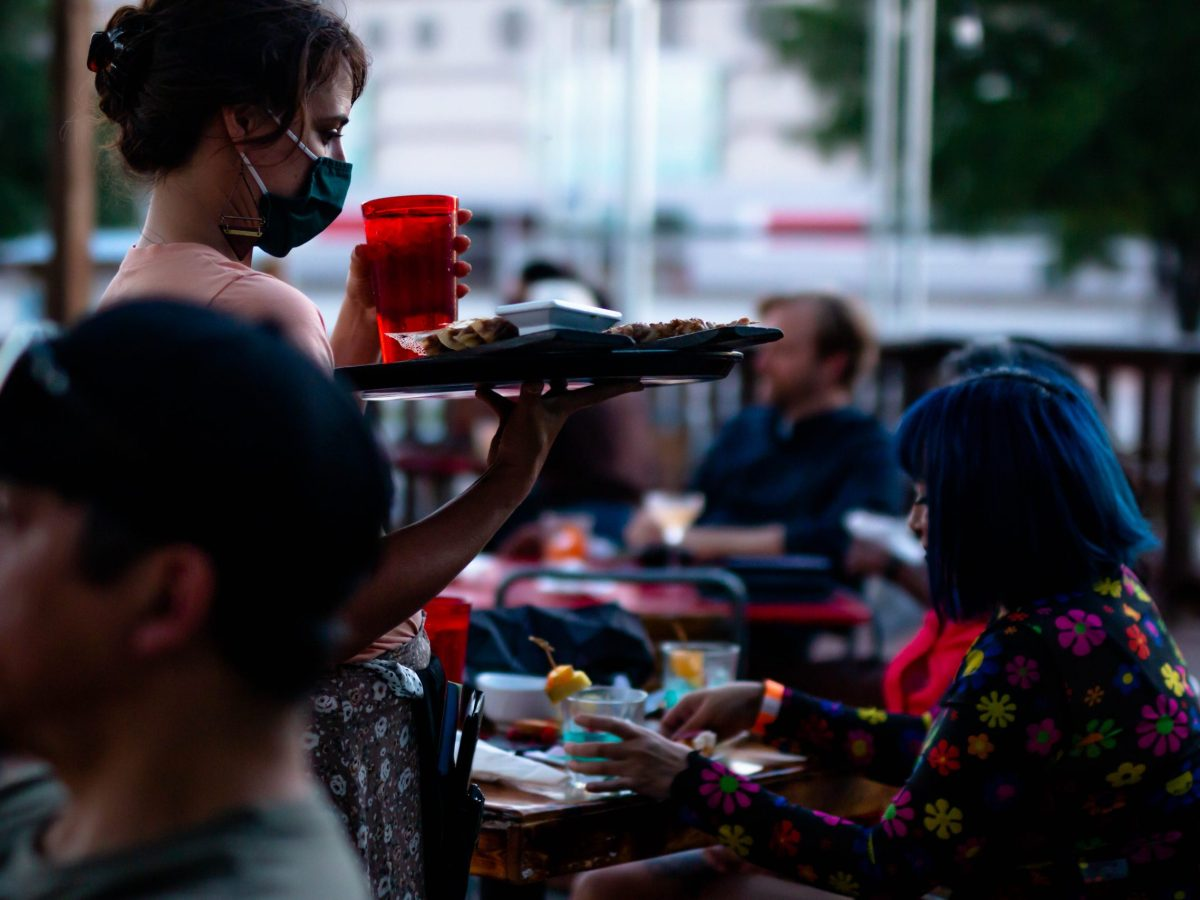 A server at The Cherrity Bar brings drinks to guests seated on their outdoor deck area. The bar and restaurant started a concert series in April to reignite the live in-person music scene in town.