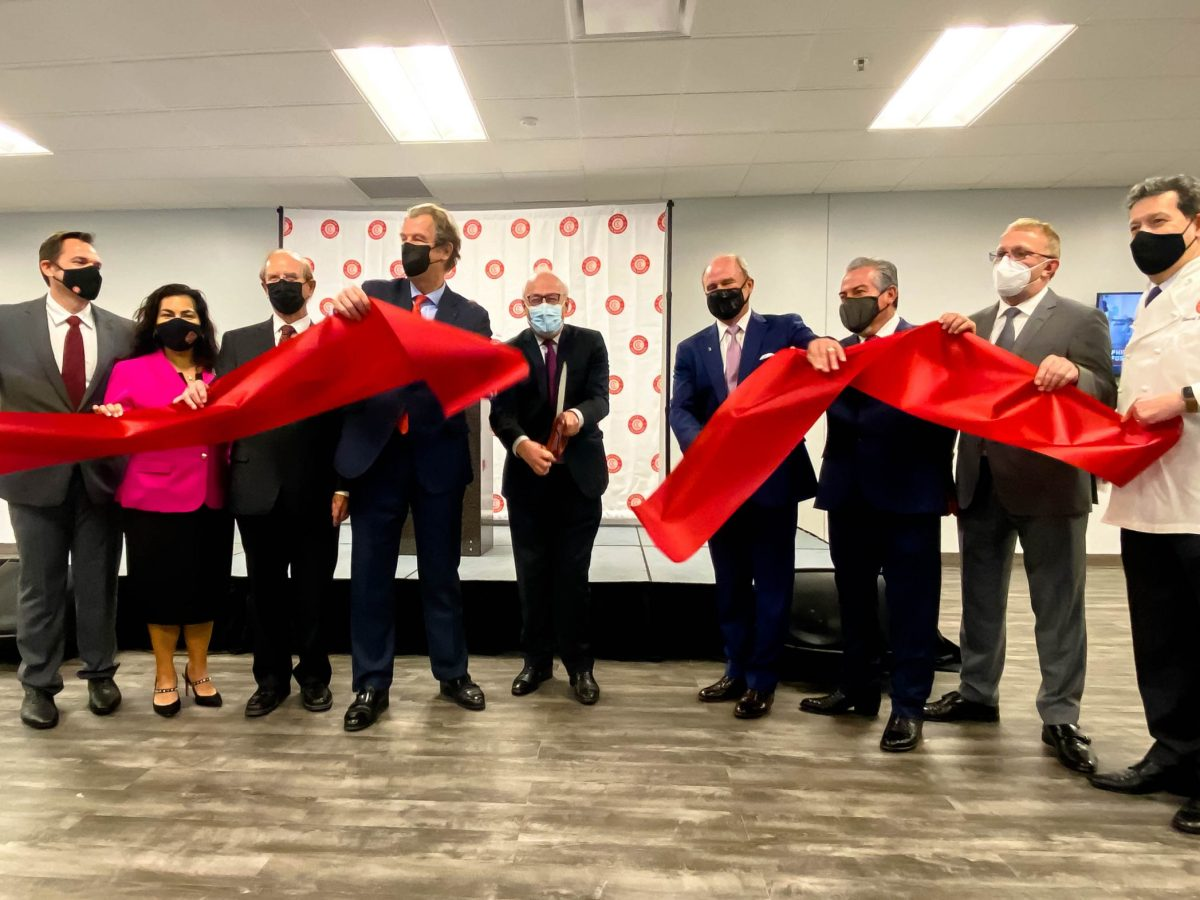 Philippe Etienne, French Ambassador to the United States (center) cuts a red ribbon with big scissors marking the grand opening of Cuisine Solutions.