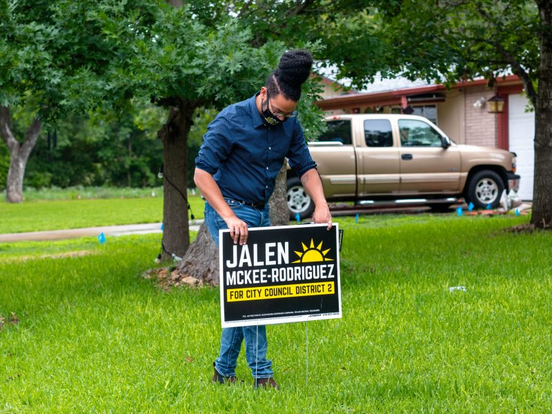 City Council (D2) hopeful, Jalen McKee-Rodriguez installs yard sign in a supporter's front lawn. McKee-Rodriguez canvassed on a rainy Saturday speaking with residents in District 2.