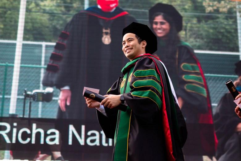 Un diplômé de la classe inaugurale de l'École de médecine ostéopathique sourit en traversant la scène après avoir reçu son diplôme.  samedi 8 mai 2021