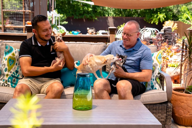 Jerry and Danny Lamb Esquivel play with their three dogs, Luna, Lupe and Nico in their backyard.