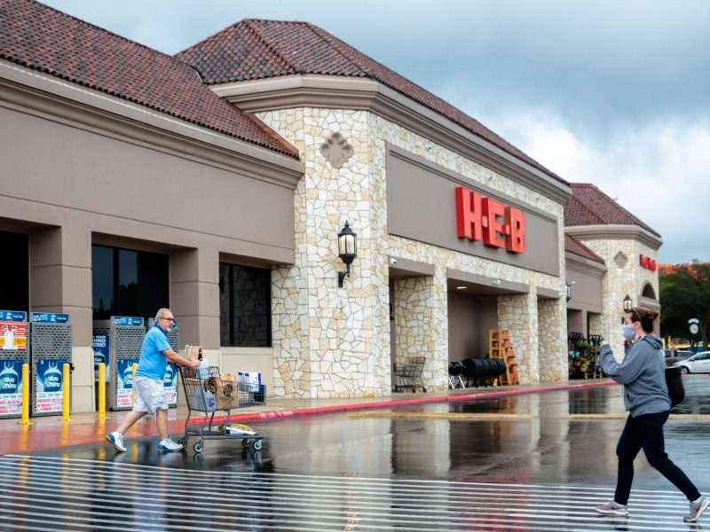 A customer exits the H-E-B in Lincoln Heights without a mask as another customer walks toward the entrance wearing a mask.