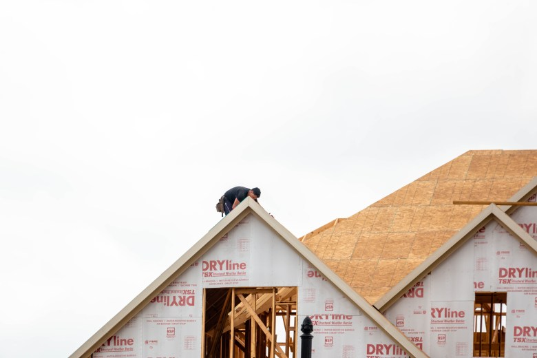 A construction worker is perched on the roof of a home in the new residential neighborhood in North East San Antonio called Coronado.