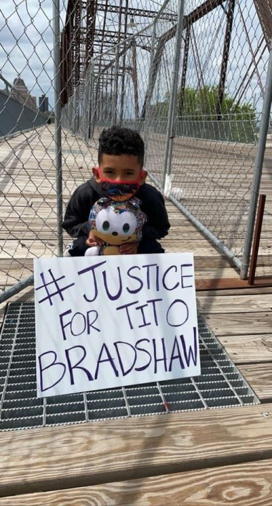 Valentino Bradshaw holds a sign calling for justice for his father, Tito Bradshaw, a cyclist who was killed by an alleged drunken driver in 2019.