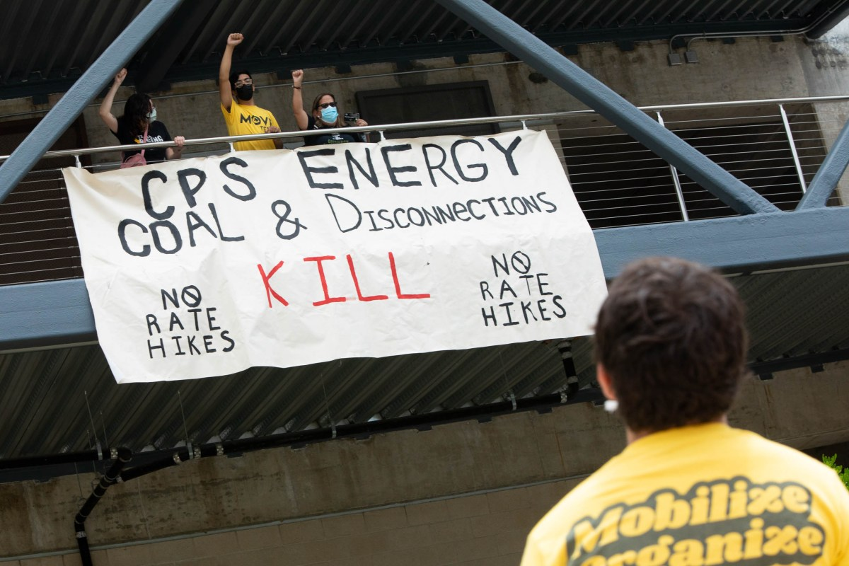 Protesters at CPS Energy's headquarters display a sign opposing disconnections, rate hikes, and the use of coal in May.
