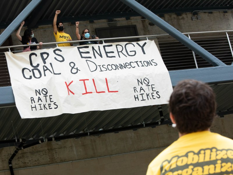 Protesters at the CPS Energy Headquarters attach a sign against disconnections, rate hikes, and the use of coal on Monday.