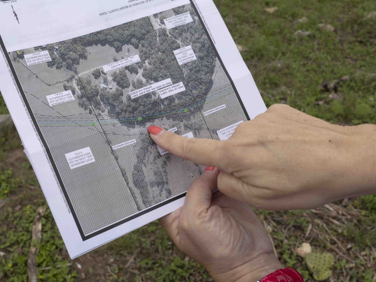 Landowner Brenda Chapman flips through pages of documents outlining the SAWS sewage line that is currently planned to run through her property which is under a conservation easement through a program with the City of San Antonio to maintain sensitive aquifer recharge zones.