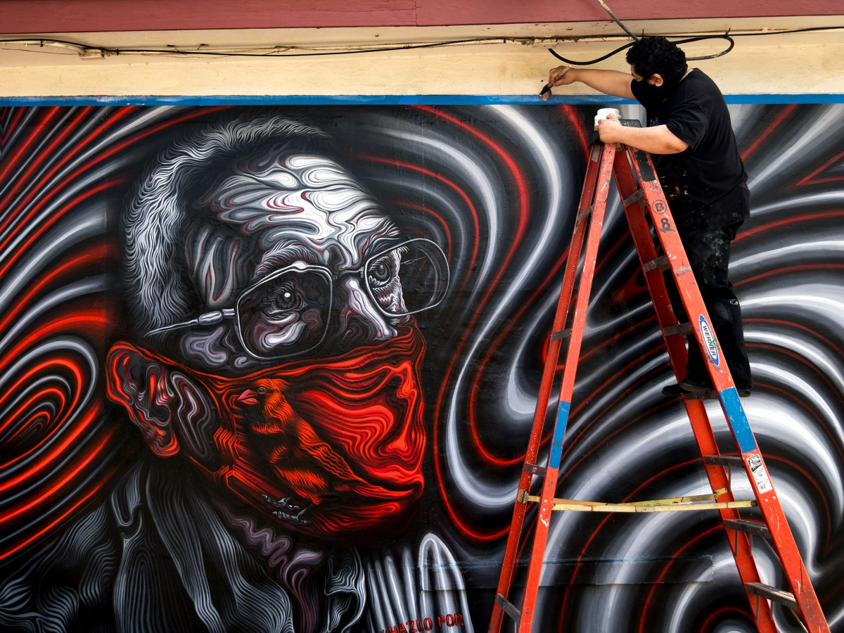 San Antonio muralist Alex Rubio installs a mural featuring SAISD trustee Arthur Valdez on South Flores Street on Thursday. The mural is one of five being installed throughout the city in an effort to encourage residents to get vaccinated against COVID-19.