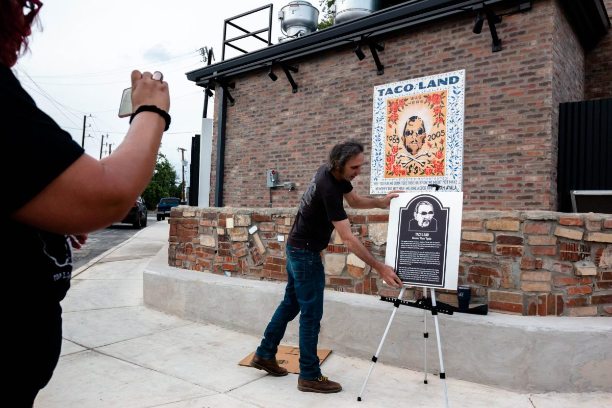 """Jeff Smith unveils the plaque honoring the life of Ramiro """"Ram"""" Ayala. The plaque will eventually be on display at the now Velvet Taco."""