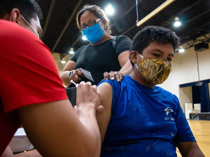 Enrique Orozco, 14, receives the Pfizer vaccine administered by UIW Nursing student Jacob Zuniga.