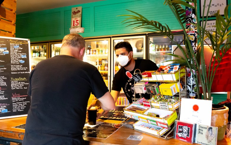 Cristian Acosta serves a beer to a customer at Dakota Ice House where he is the manager. The Eastside hangout is only a few paces away from his home.