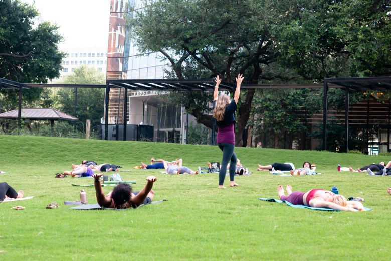 A group does yoga in Legacy Park. The newly opened outdoor space next to the Frost Tower is seeing more events and activations this year.