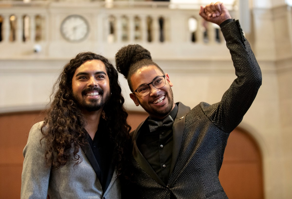 City Councilman Jalen McKee-Rodriguez (D2) raises his fist next to his husband, Nathan, during a swearing-in ceremony on Tuesday.