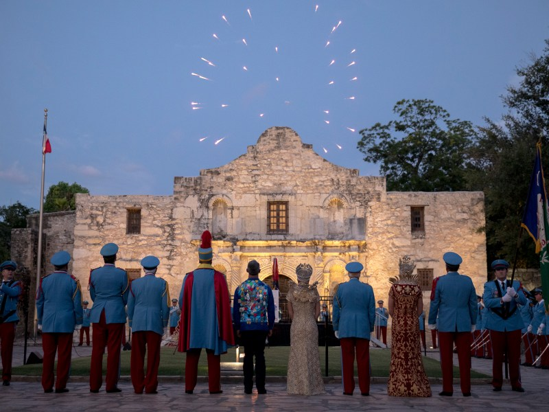 King Antonio XCVIII Phillip Peacock Bakke, fifth from left, watches fireworks with fellow Texas Cavalier members, Mayor Ron Nirenberg and royalty after his investiture at Alamo Plaza on Saturday.
